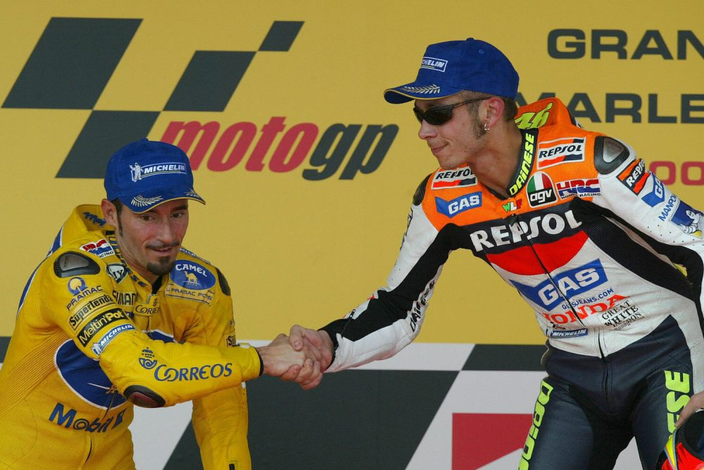 Moto GP World Champion and winner of the Moto Grand Prix of Spain, Italian Valentino Rossi (R) shakes hands with his fellow compatriot and second placed Max Biaggi on the podium 11 May 2003, in Jerez. Australian Troy Bayliss finished third. AFP PHOTO/ Pierre-Philippe MARCOU   (Photo credit should read PIERRE-PHILIPPE MARCOU/AFP/Getty Images)